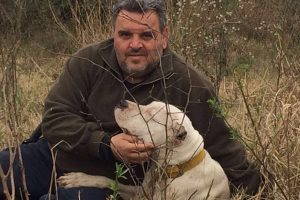 man with his white dogo argentino